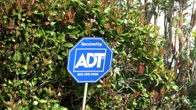 Zoom in to sign reading Secured by ADT for the burglar alarm and home security company ADT in front of a suburban home in San Ramon California March...