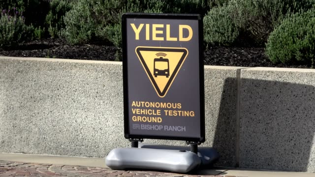 Zoom in to sign reading Yield Autonomous Vehicle Testing Ground warning drivers to yield to selfdriving shuttles being tested at the Bishop Ranch...