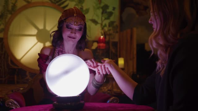 vídeos y material grabado en eventos de stock de zoom in to smiling fortune teller with crystal ball reading palm of customer in nightclub / provo, utah, united states - calcular