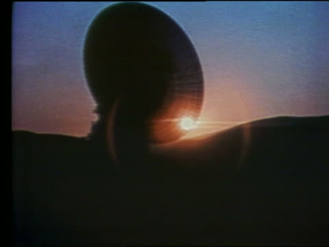 zoom in to sunset seen through silhouette of satellite dish - 1997 stock videos & royalty-free footage