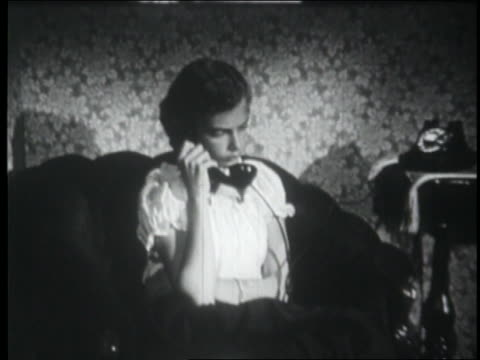 b/w 1953 zoom in to teen girl sitting in armchair + talking on telephone - one teenage girl only stock videos & royalty-free footage