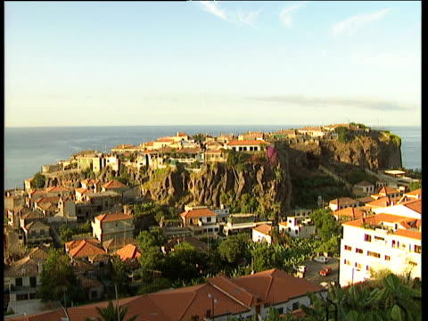 zoom in to terracotta coloured houses on rocky cliffs surrounded by trees calm sea in background madeira - ポルトガル点の映像素材/bロール