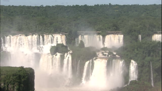 Zoom in to tourists walking over public walkway overlooking Iguazu Falls, border of Brazil and Argentina