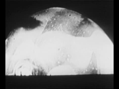 zoom in to tower and building on island subjected to first us test of hydrogen bomb / montage detonation w/ vo explosion detonation resembles a large... - radioaktiver niederschlag stock-videos und b-roll-filmmaterial