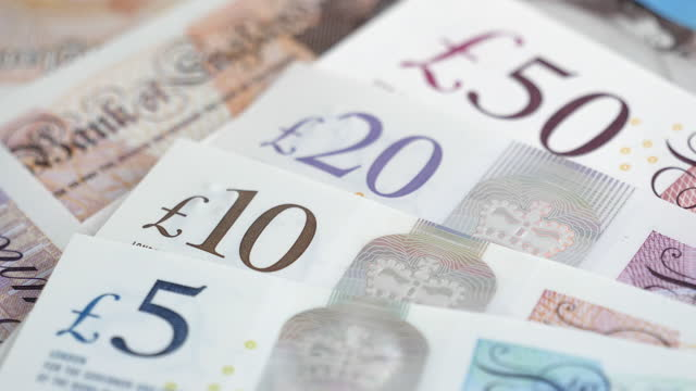 zoom in to various uk bank notes - pound sterling symbol stock videos & royalty-free footage