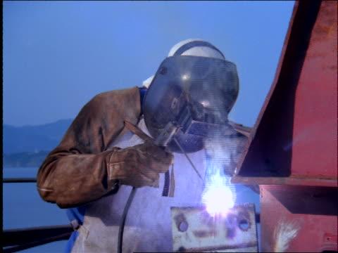 zoom in to welder in mask welding outside / Brazil