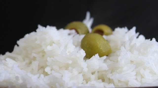 zoom in to white rice garnished with green olives - high contrast stock videos & royalty-free footage