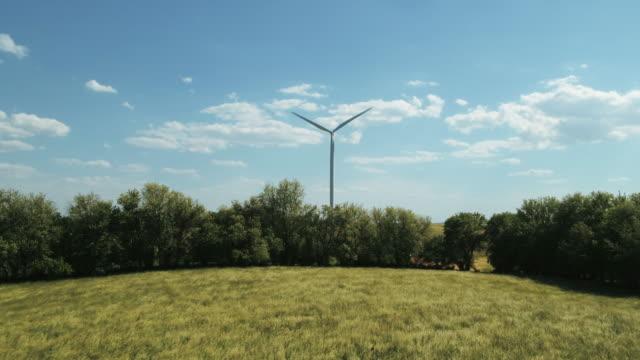 Zoom in to wind turbine in breezy meadow