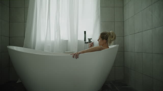 vídeos de stock e filmes b-roll de zoom in to woman eating chocolate and relaxing in bathtub / lehi, utah, united states - lehi