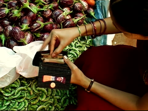 zoom in to woman removing banknotes from wallet to buy peas at outdoor market / bangalore, karnataka, india - bangalore stock videos and b-roll footage