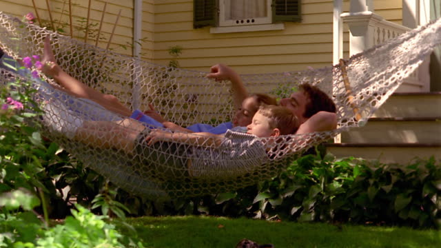 vidéos et rushes de zoom in to ms young boy + older girl sleeping on hammock with man in middle outdoors - hamac