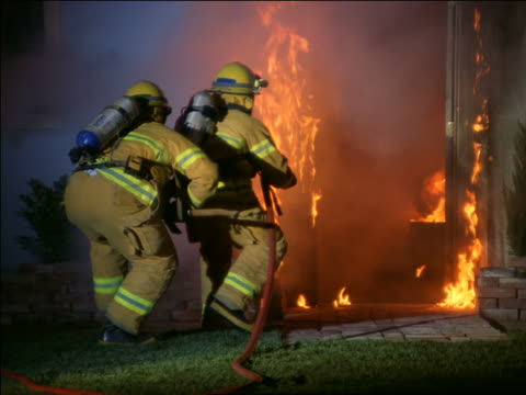 zoom in two firemen advancing on burning house spraying water on fire - firefighter stock videos and b-roll footage