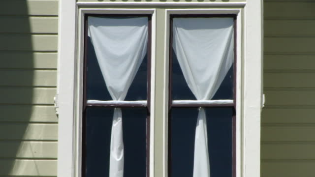 zoom in view of a window with two tied up white curtains from the outside - white点の映像素材/bロール