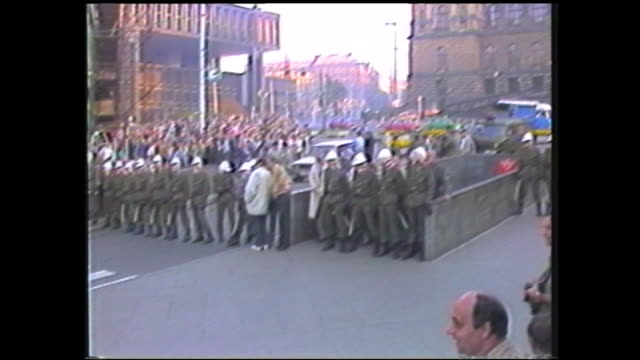 zoom in view of czech flag held up by the crowd, zoom out and pan to the riot police standing in a row opposite of them at wenceslas square - czech republic stock videos & royalty-free footage