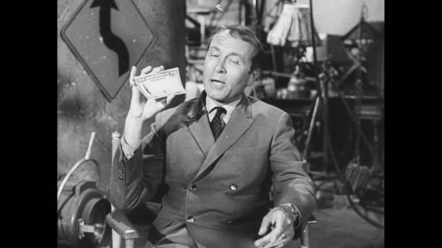 zoom in view of howard morris sitting on fold up chair on set, holding u.s. saving bonds in hand and advocating for the audience to purchase them - film set stock videos & royalty-free footage