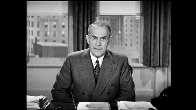 zoom in view of man in suit sitting behind office desk in front of windows, putting down the telephone and speaks to the camera - 1940 1949 stock-videos und b-roll-filmmaterial