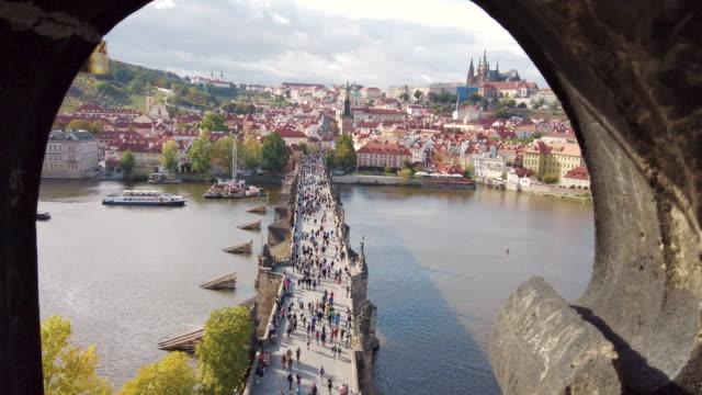 zoom in view of vltava river and charles bridge in prague in czech republic - praga video stock e b–roll