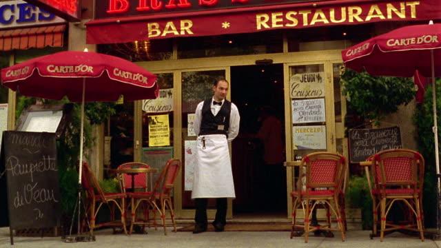 vídeos de stock, filmes e b-roll de zoom in wide shot portrait waiter standing in front of restaurant / cannes, france - garçom