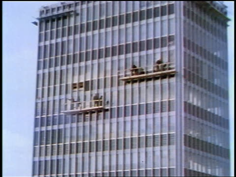 1957 zoom in window washers on scaffolding on skyscraper - cleaner stock videos and b-roll footage