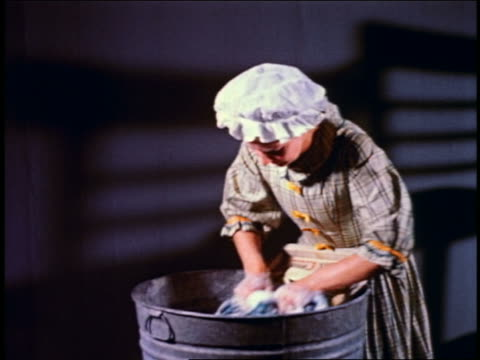 vídeos y material grabado en eventos de stock de 1950 reenactment zoom in woman in colonial clothing washing clothes with washing board in large metal tub - 18th century