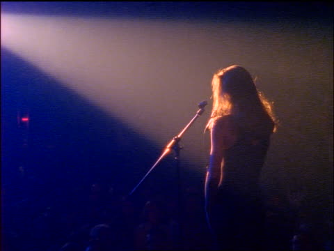 vidéos et rushes de rear view zoom in woman in spotlight on stage singing to audience - rock moderne