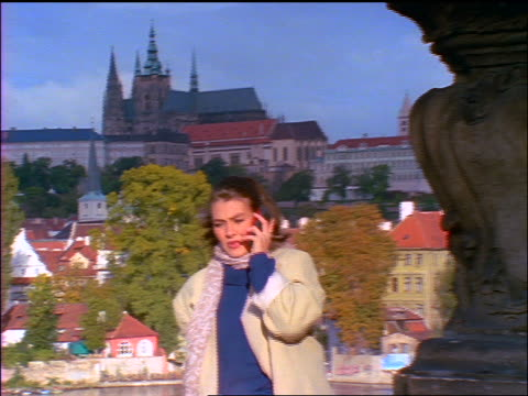 zoom in woman talking + laughing on cellular phone outdoors / prague castle in background / czech republic - castle stock videos & royalty-free footage