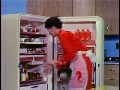 1955 zoom in woman walking across kitchen + removing aluminum-wrapped meat from refrigerator