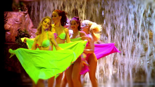 MS zoom in women in bikini costumes dancing on stage with waterfall in background