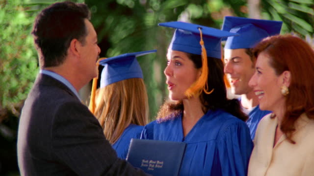 MS zoom in young Hispanic woman wearing cap + gown hugging + kissing parents / Florida