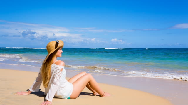 WS zoom in, young woman looking out over tropical beach