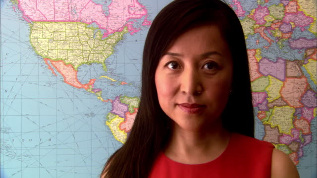 zoom in zoom out asian woman standing in front of world map - world politics stock videos & royalty-free footage