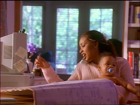 zoom in + zoom out black woman holding baby + talking on telephone at home while using  computer - sladdlös telefon bildbanksvideor och videomaterial från bakom kulisserna
