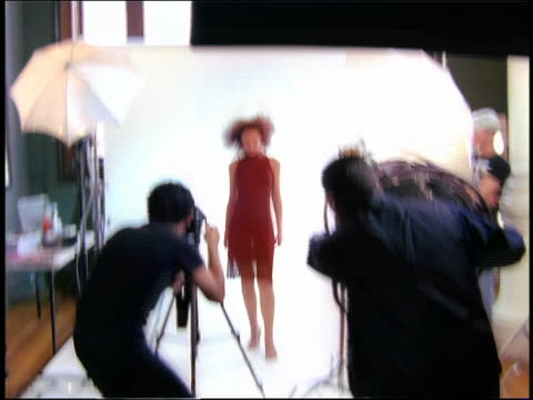 Zoom in zoom out model posing in studio for photographer and fan operator in foreground /speed change from fast to normal