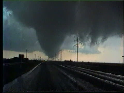 zoom in + zoom out of tornado moving in sky past road - extreme weather stock videos & royalty-free footage