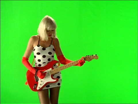 zoom in + zoom out of woman playing guitar with chroma key background