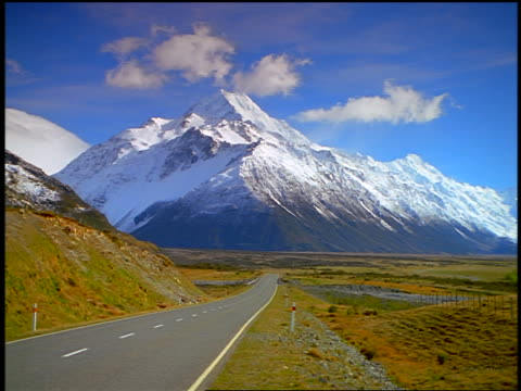zoom in + zoom out paved road leading to snow-covered Mt. Cook / Southern Alps, South Island / New Zealand