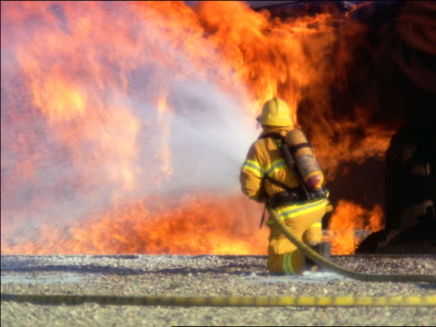 ms zoom in zoom out rear view firefighter spraying water from hose onto large fire - one man only stock videos & royalty-free footage