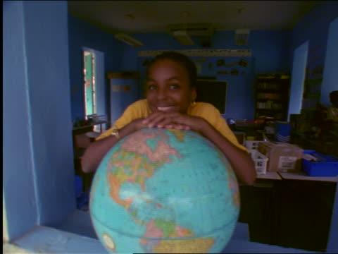 portrait zoom in + zoom out smiling black girl leaning on globe in school window / st. john, virgin islands - st. john virgin islands stock videos & royalty-free footage