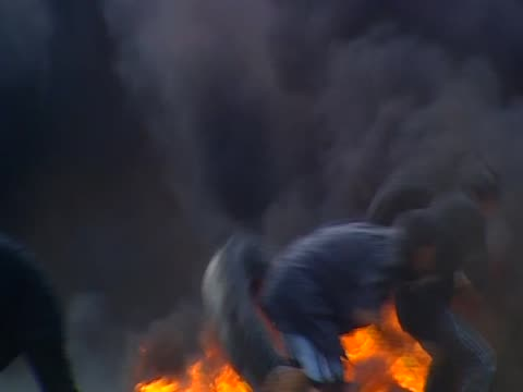 zoom into antigovernment protesters burning rubber tires during violent clash with armed government forces thailand 15 may 2010 - violence stock videos & royalty-free footage