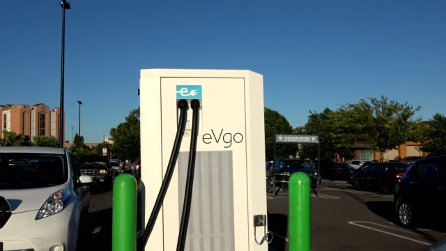 vídeos de stock, filmes e b-roll de zoom into evgo electric vehicle charging station in a parking lot in dublin california 2018 - posto de carregamento de veículos elétricos
