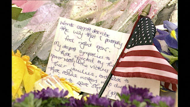 zoom into handwritten message left with a us flag among the flowers laid in tribute to 9/11 victims in london; september 13th, 2001. - national flag stock videos & royalty-free footage