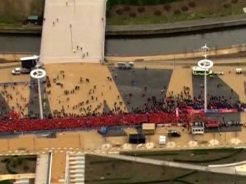 zoom into people starting the public around the olympic park in stratford - ロンドン ストラトフォード点の映像素材/bロール