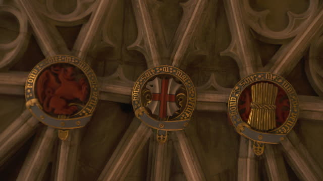 Zoom into symbolic motifs on the ceiling of St George's Chapel Windsor Castle including a dragon the St George's Cross and a sheath of wheat...