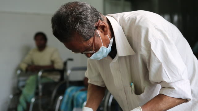 zoom on a doctor in the hospice for people in poverty helping leprosy patients it is located in the northeast of india near the city of bagdogra... - chirurgenkappe stock-videos und b-roll-filmmaterial