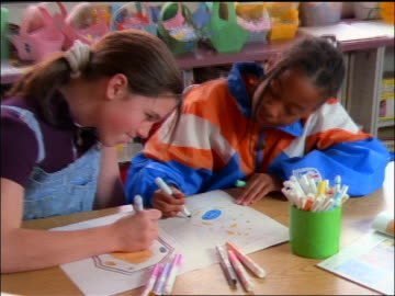 zoom out 2 black + white girls sitting at desk doing artwork together in classroom - zoom out stock-videos und b-roll-filmmaterial
