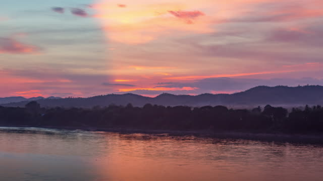 zoom out 4k time lapse:sunset above the mountain and river with beautiful reflection of twilight sky - laos stock videos & royalty-free footage