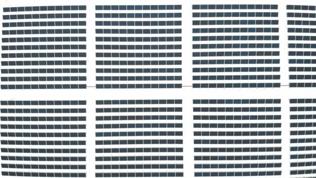 vidéos et rushes de zoom sur des images aériennes de panneaux solaires sur le toit d'une usine - toiture