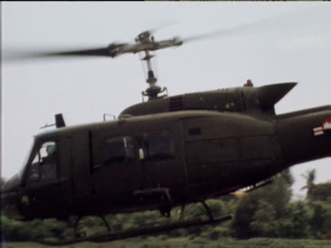 vídeos de stock, filmes e b-roll de zoom out and pan left as helicopter takes off bound for frontline cambodia mar 75 - cambodia