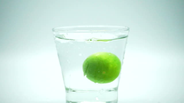 zoom out and reverse of green lemon drop into glass of water in slow motion. - reverse motion stock videos & royalty-free footage