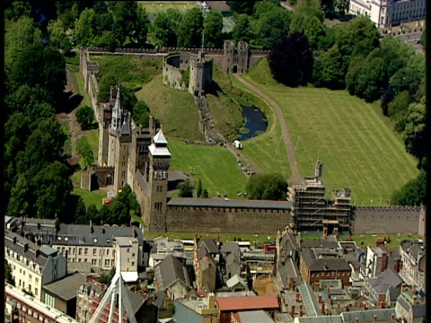zoom out and track backwards over ruins at cardiff castle to millennium stadium with open roof - millennium stadium stock videos & royalty-free footage